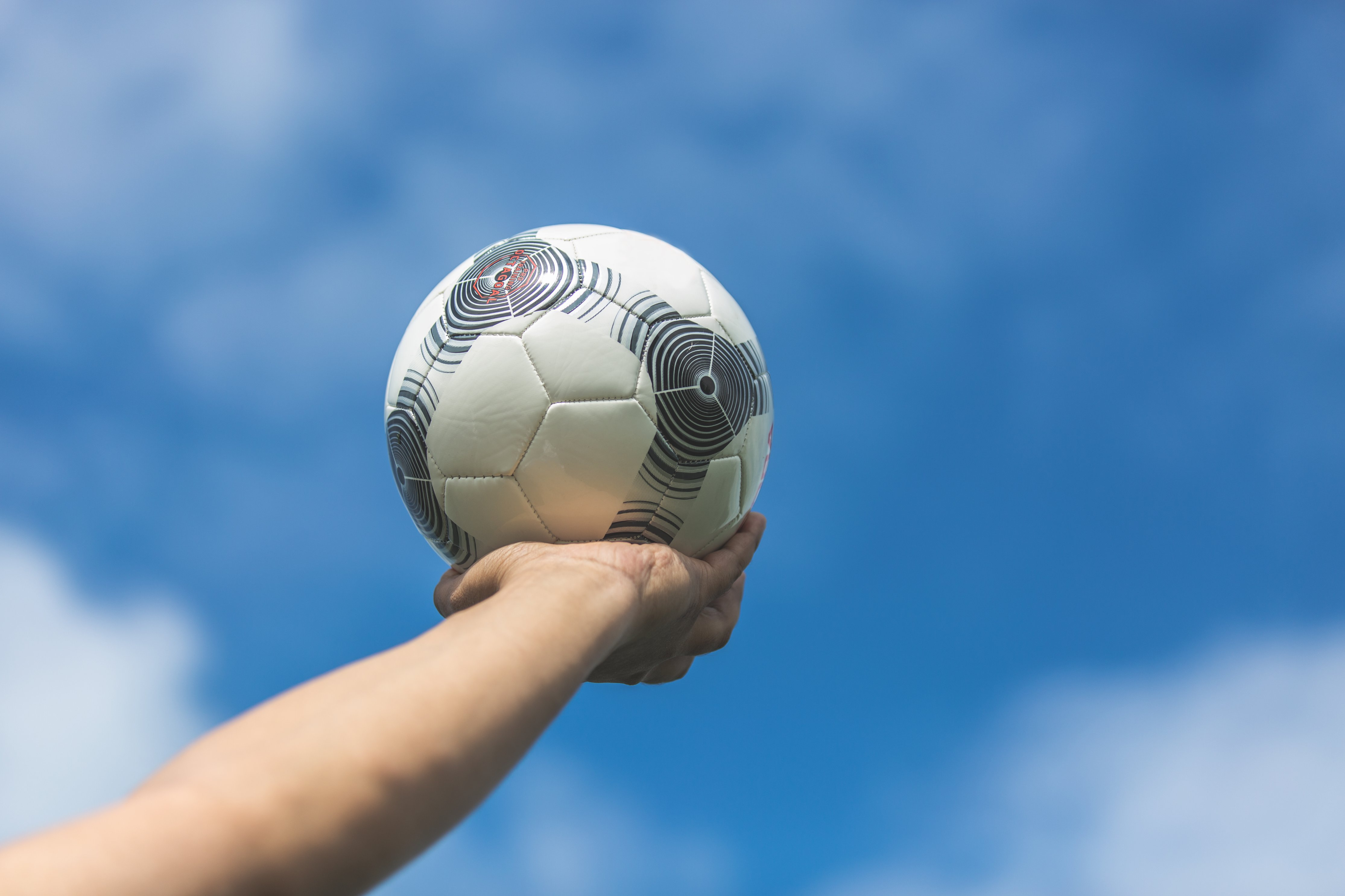 holding-out-soccer-ball-to-the-blue-sky 4460x4460